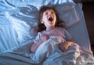 Bild von schreiendem Mädchen im Bett