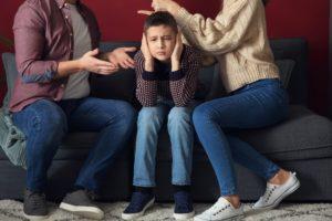 Bild von streitenden Eltern im Beisein des geplagten Kindes