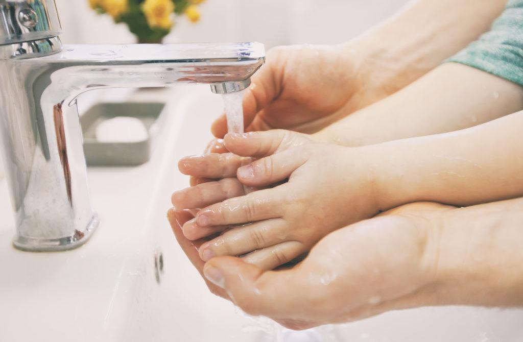 Bild von Vater der seinem Kind beim Händewaschen hilft