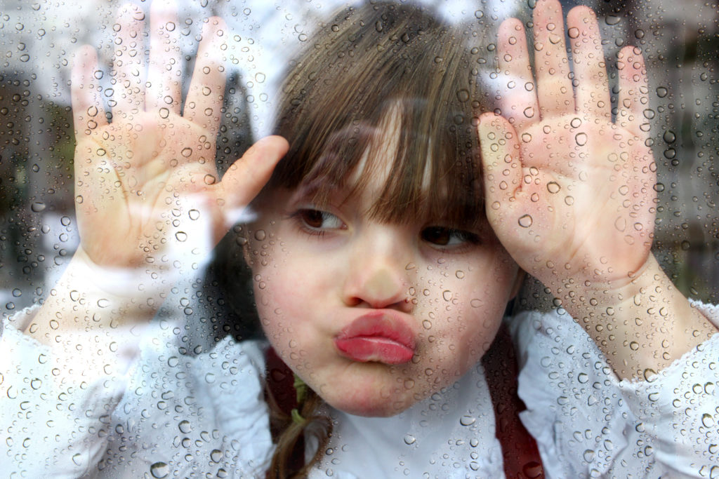 Kind schaut gelangweilt aus dem Fenster