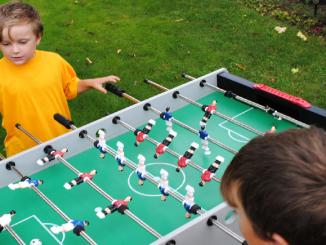 Bild zwei Kinder beim Kicker spielen