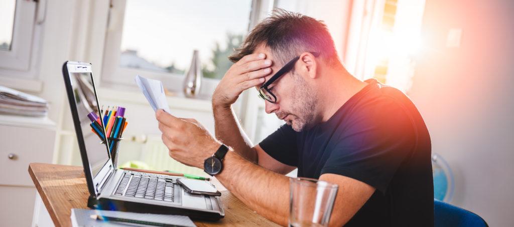 Vater sitzt vor Laptop und zerbricht sich Kopf über einen Antrag