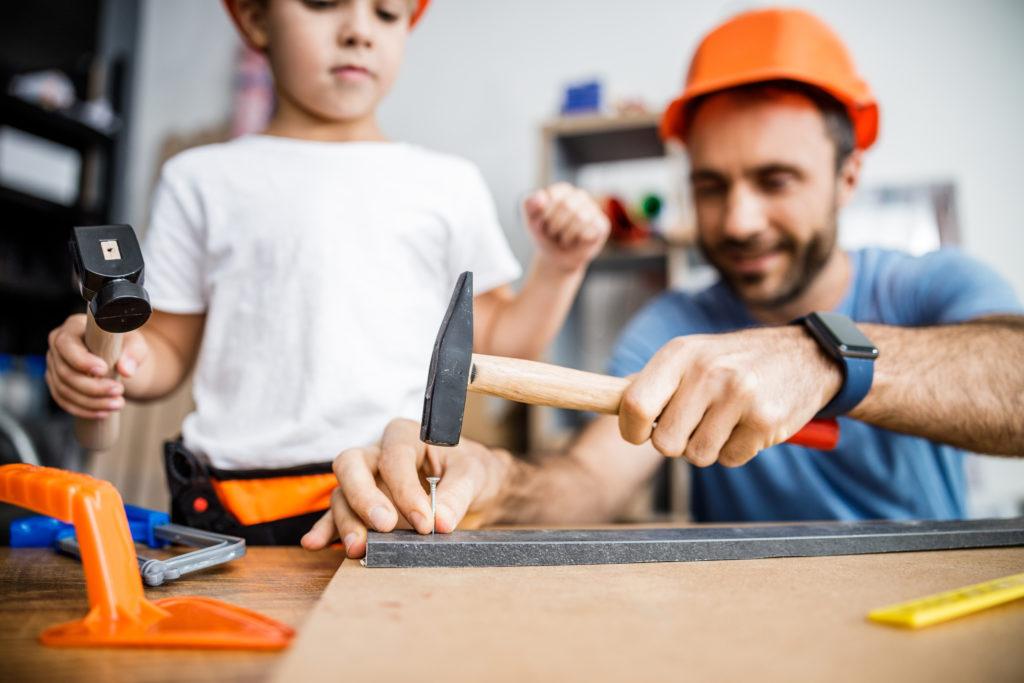 Bild von Vater und Sohn, die gemeinsam werken mit Hammer und Nagel
